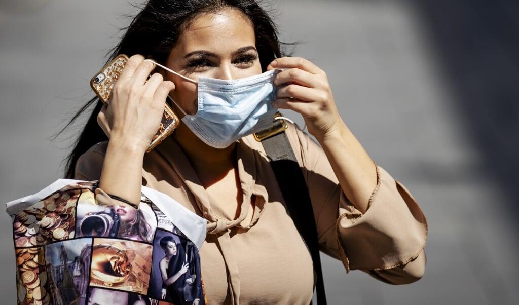 ROTTERDAM - Mensen met mondkapjes in het centrum van Rotterdam. In een aantal winkelgebieden in Rotterdam is een verplichting om niet-medische mondkapjes te dragen. De verplichting geldt van 6.00 uur tot 22.00 uur voor iedereen van dertien jaar en ouder. ANP ROBIN VAN LONKHUIJSEN  (beeld Robin van Lonkhuijsen)