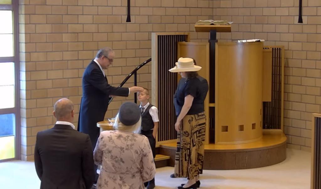 Bij de doop moet de 9-jarige jongen zijn hoofd iets omhoog doen.  (beeld Youtube)