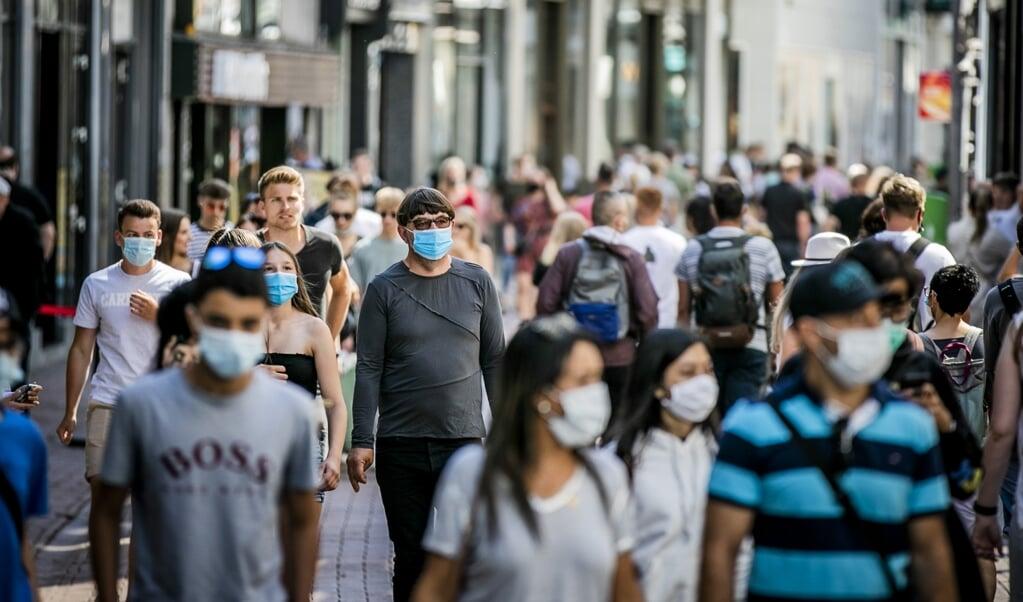 Winkelend publiek in de Kalverstraat in Amsterdam. Op vijf plekken in de stad is het dragen van een mondkapje inmiddels verplicht gesteld.  (beeld anp / Remko de Waal)