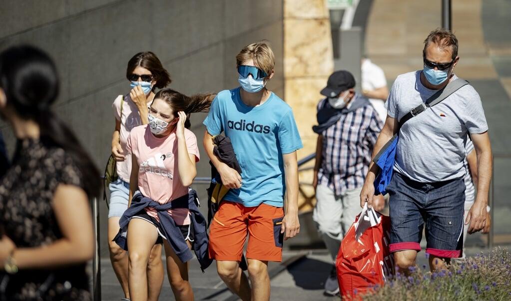 Mensen met mondkapjes in het centrum van Rotterdam. In een aantal winkelgebieden in Rotterdam is een verplichting om niet-medische mondkapjes te dragen. De verplichting geldt van 6.00 uur tot 22.00 uur voor iedereen van dertien jaar en ouder.   (beeld anp / Robin van Lonkhuijsen)