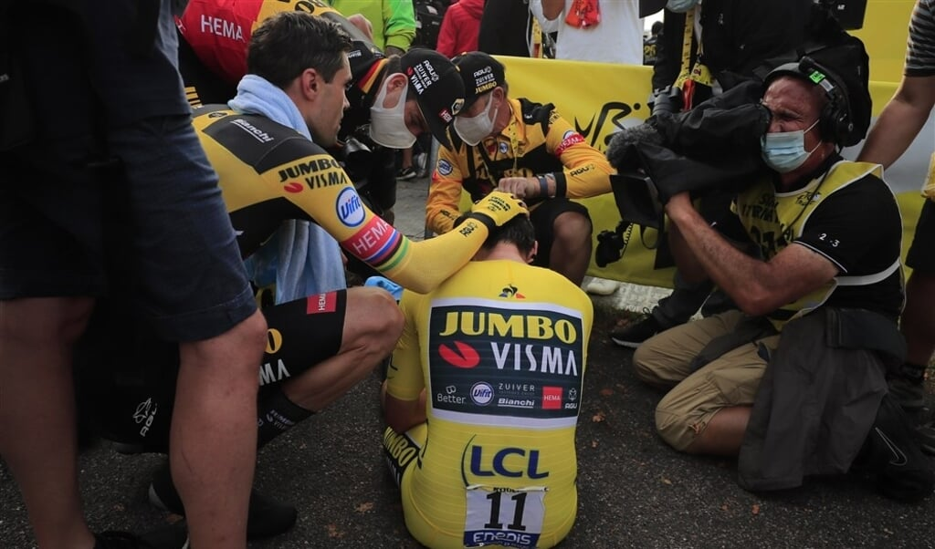 Primoz Roglic zit verslagen op de grond. Hij wordt getroost door Tom Dumoulin.  (beeld Hollandse Hoogte / AFP)