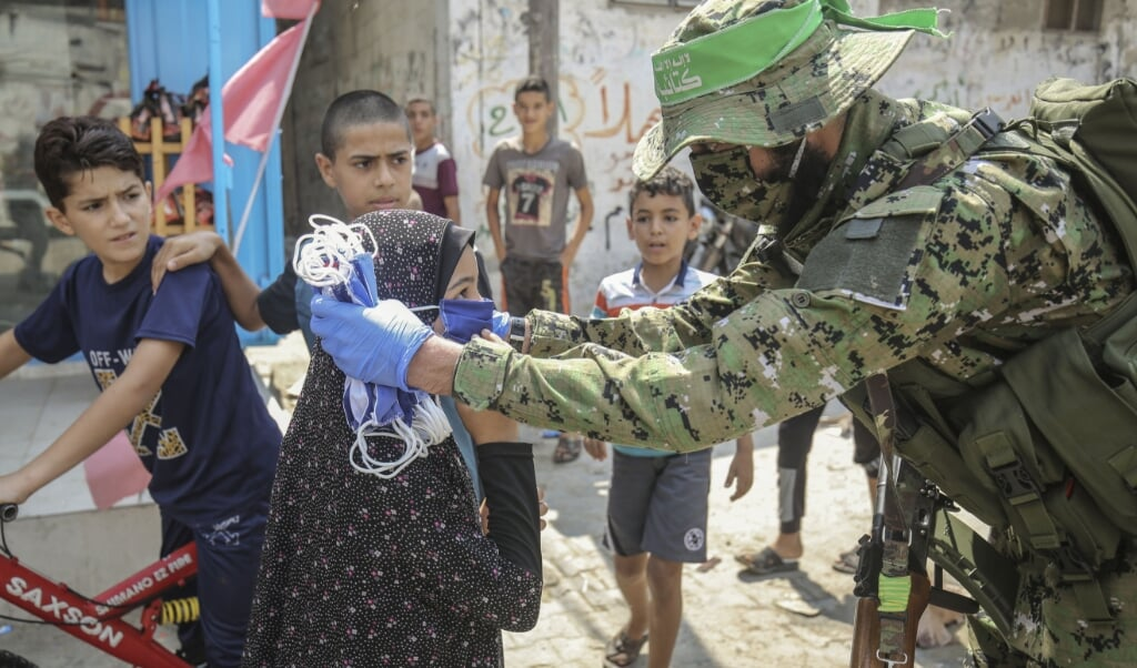 Een strijder van een gewapende vleugel van Hamas deelt in de Gazastrook beschermende maskers uit op straat .  (beeld afp / Said Khatib )