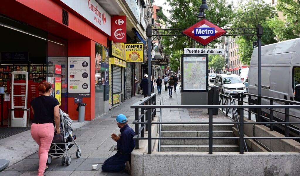 <p>Een bedelaar in de buitenwijk Vallecas in Madrid. Alleen voor werk, school en strikt noodzakelijke boodschappen mogen de bewoners van sinds maandag hun buurt nog uit.</p>  (beeld epa / V&atilde;&shy;tor Lerena)