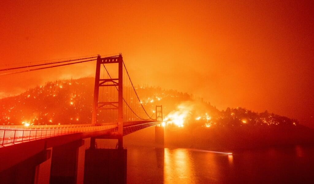 <p>Wind jaagt het vuur op bij Lake Oroville en verwoest de elektriciteitskabels die boven de grond lopen.</p>  ( beeld AFP/Josh Edelso)
