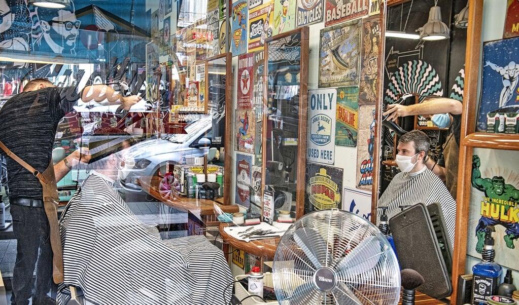 <p>Een barbershop op de Nieuwe Binnenweg in Rotterdam. Zowel de klant als de kapper draagt een mondkapje. Verder heeft de zaak plexiglas, extra ventilatie en wordt er alleen gekapt op afspraak.</p>  (beeld Guus Dubbelman)