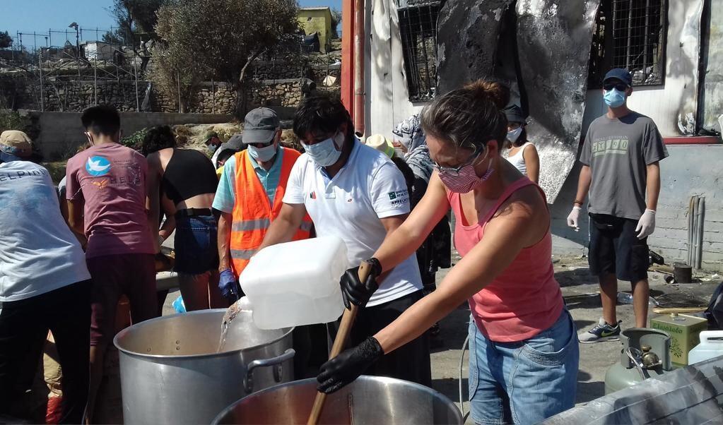 <p>Vrijwilligers van de lokale vereniging Sinipraxi delen voedsel uit aan de vluchtelingen nadat het kamp Moria was afgebrand.</p>  (beeld Sinipraxi)
