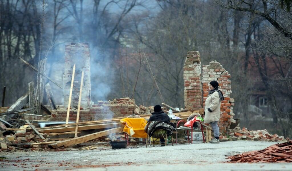 Dakloos geworden Kroatische vrouwen voor hun voormalige woning in Petrinja.   (beeld afp / DAMIR SENCAR )