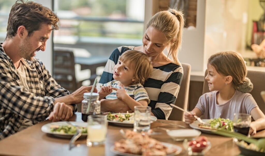 Young happy family enjoying in their lunch time at dining table.  (beeld istock)