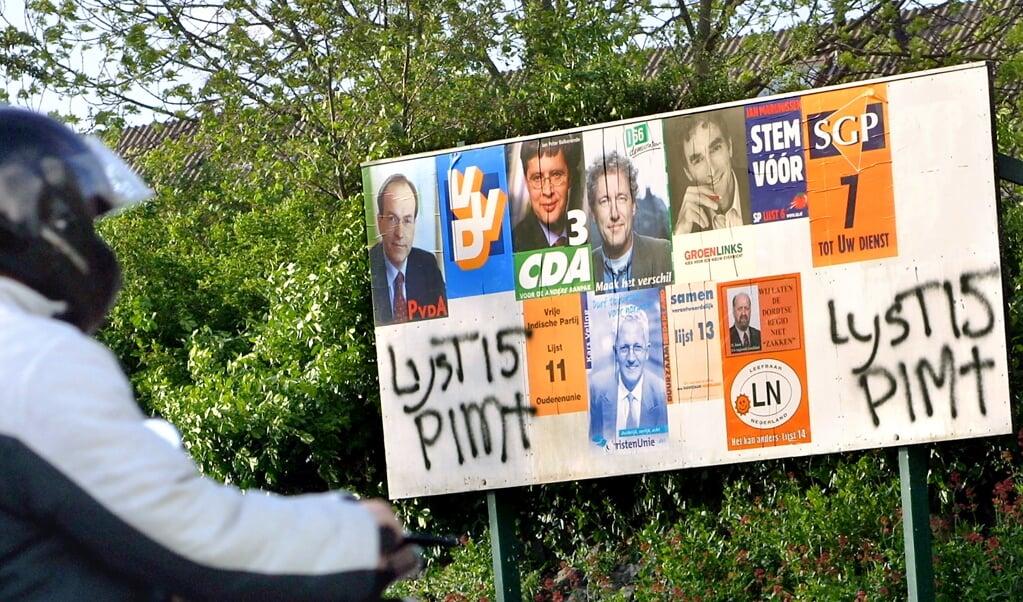Vlak voor de Tweede Kamerverkiezingen in 2002 werd Pim Fortuyn op 6 mei 2002 vermoord, de lijsttrekker van de LPF, de Lijst Pim Fortuyn. Op dit bord ontbreekt de poster van de LPF, maar een aanhanger heeft met de verfspuit Lijst 15 Pim† twee keer op een lege plek gespoten.   (beeld novum / Dirk Hol)