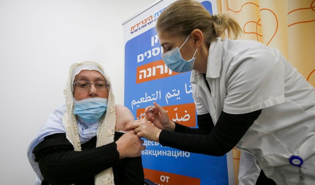 Een druzische vrouw uit een dorp op de Golan-hoogte krijgt haar coronavaccinatie, afgelopen week.  (beeld afp / Jalaa Marey)