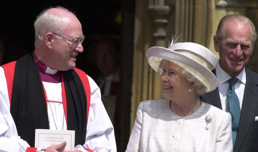 George Carey (links) in gesprek met de Britse Queen Elizabeth op een archieffoto uit 2002.  (beeld afp / Martin Hayhow)