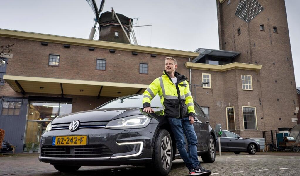 Henri bij zijn laatste auto-van-de-zaak, een VW e-Golf.  (beeld Niek Stam)
