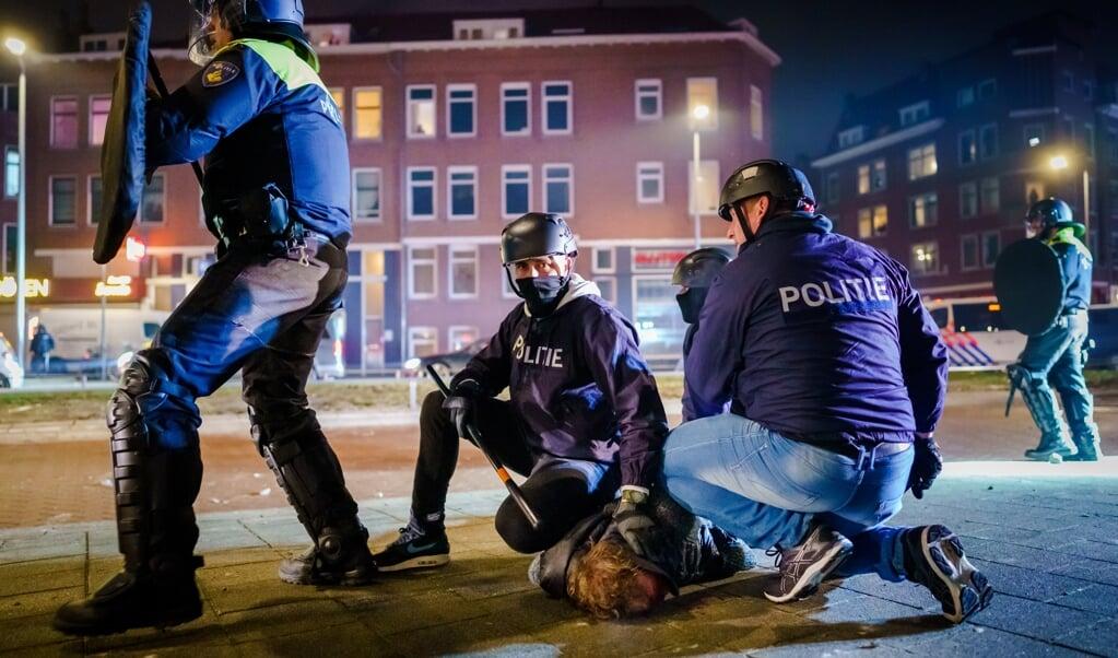 De politie arresteert een relschopper op de Beijerlandselaan in Rotterdam.  (beeld anp / Marco de Swart)