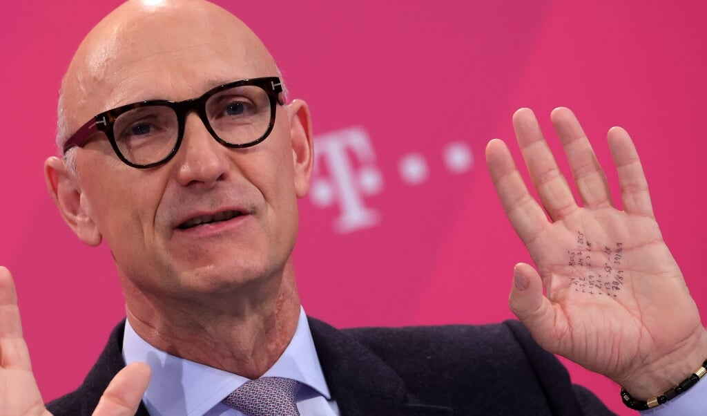 CEO Timotheus Höttges met achter hem het logo van T-Mobile.  (beeld epa / Friedemann Vogel)