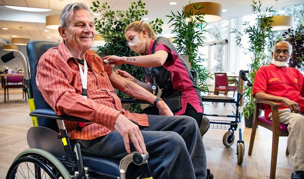 Voormalig psycholoog Bart Uijterlinde (91) ondergaat lachend de prik. De bewoner van een verpleeghuis in Haarlem voelt zich daarna 'kiplekker', zegt hij. Jamiel Ramzam kijkt toe.  (beeld Guus Dubbelman)