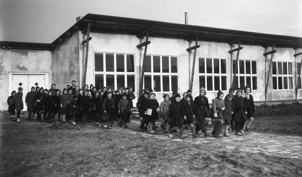 Kinderen verlaten het noodgebouw van de latere Koningin Julianaschool.  (beeld nationaal archief)