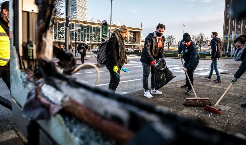 Vrijwilligers helpen in het centrum van Eindhoven bij het opruimen van de schade, na de rellen van afgelopen zondag.  (beeld anp / Rob Engelaar)
