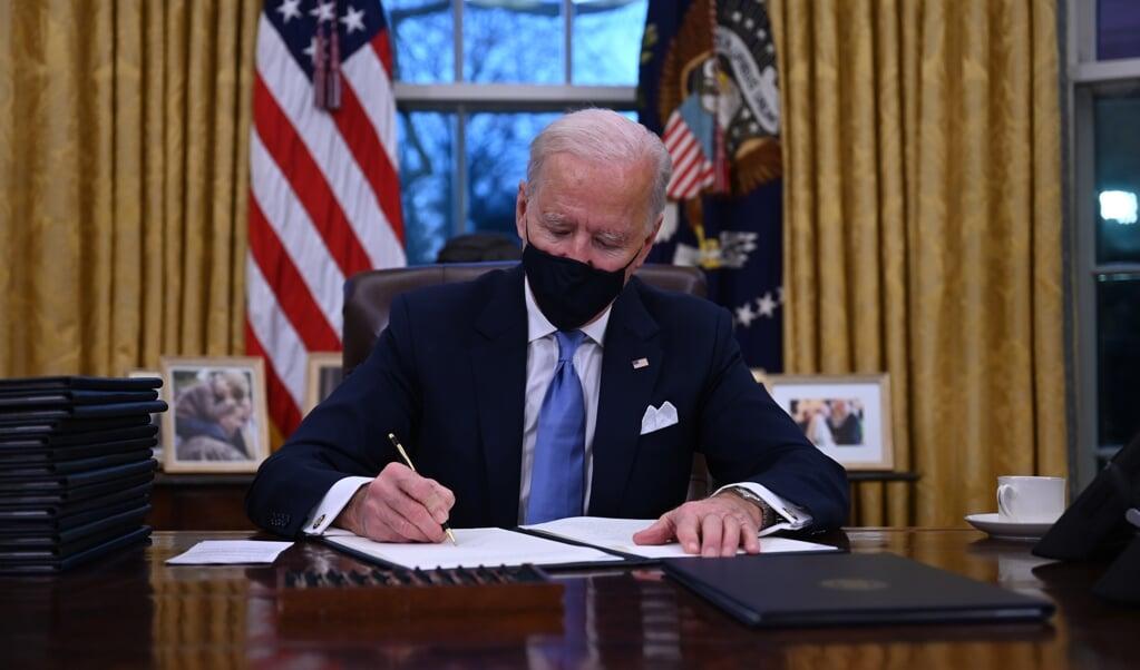 Op zijn eerste werkdag in het Witte Huis ondertekent president Joe Biden een aantal decreten.  (beeld afp / Jim Watson)