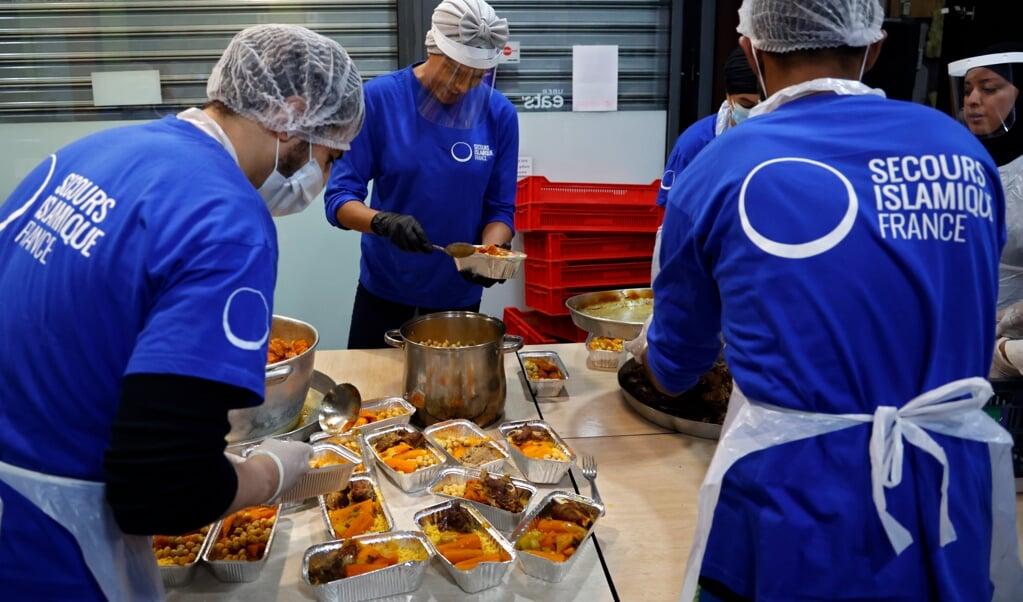 Vrijwilligers van de Franse tak van Islamic Relief bereidden vorig jaar tijdens de Ramadan voedsel voor moslims die arm zijn.  (beeld Thomas Coex / afp)
