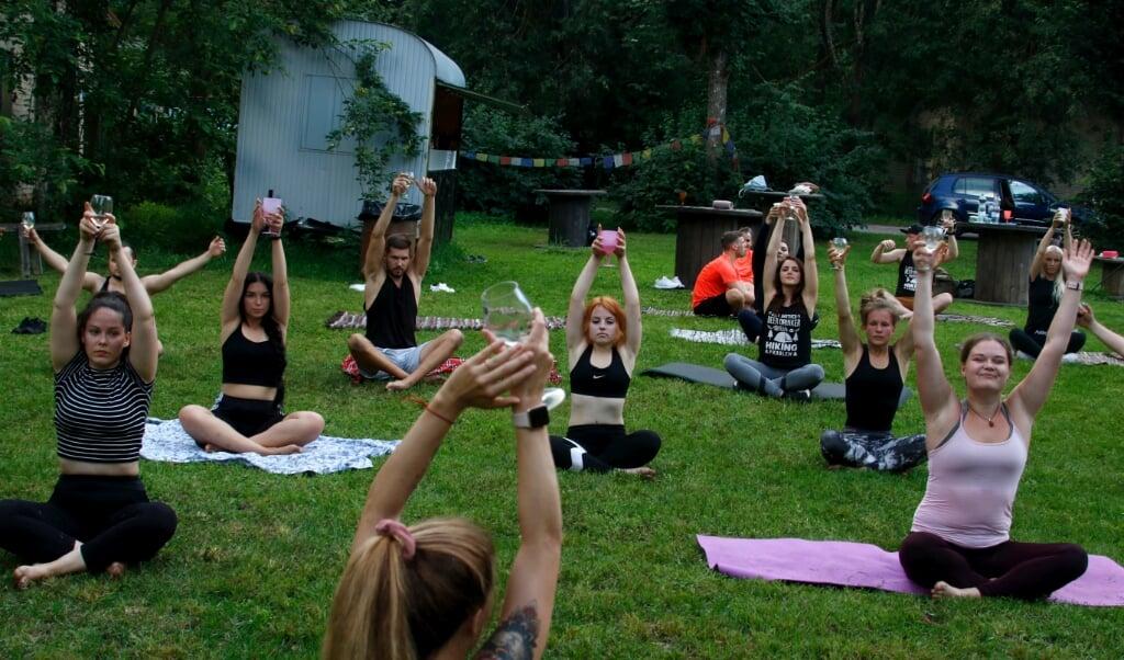 2020-08-08 20:19:08 epa08592499 People practice during a Wine Yoga event in Riga, Latvia, 08 August 2020.  EPA/Valda Kalnina  (beeld Epa/valda Kalnina)
