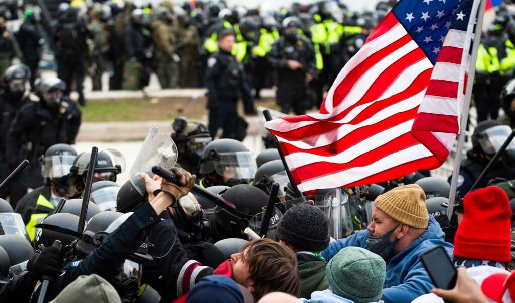 Trump-aanhangers vechten met politieagenten tijdens de bestorming van het Capitool woensdag.  (beeld afp / Roberto Schmidt)