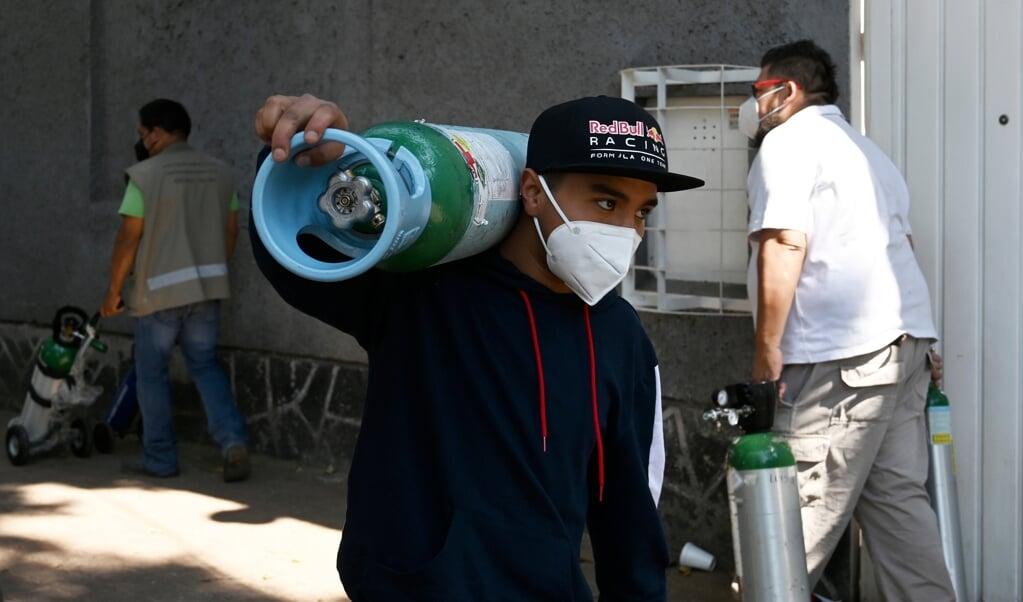 Een rij voor het bijvullen van zuurstoftanks in Mexico City. Mexico heeft als vierde land in de wereld melding gemaakt van meer dan 150.000 doden door het coronavirus.  (beeld afp / Rodrigo Arangua)