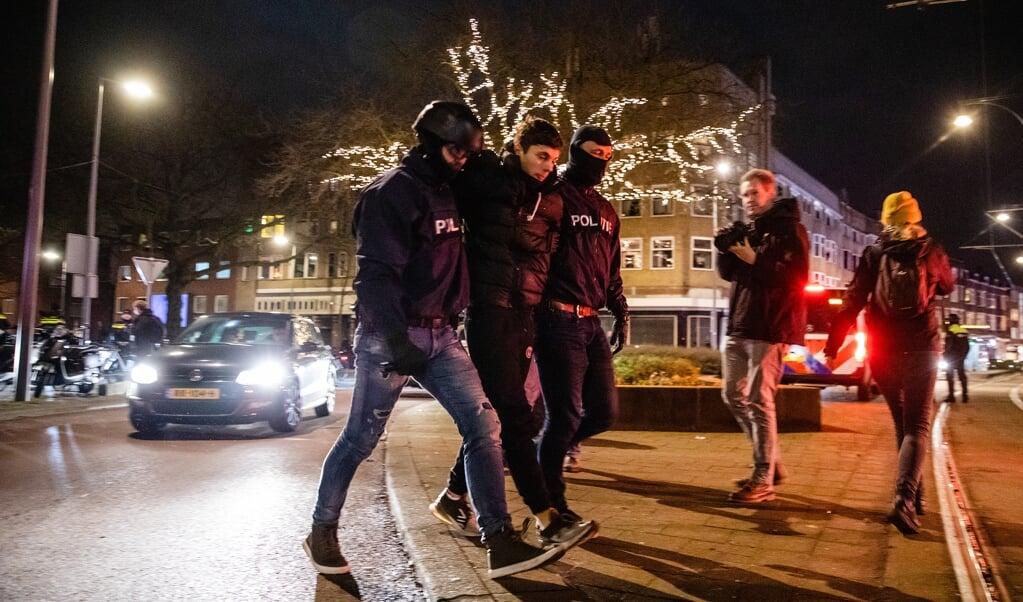 De politie houdt dinsdagavond in Rotterdam-Zuid een man aan wegens samenscholing.  (beeld anp / Jeffrey Groeneweg)
