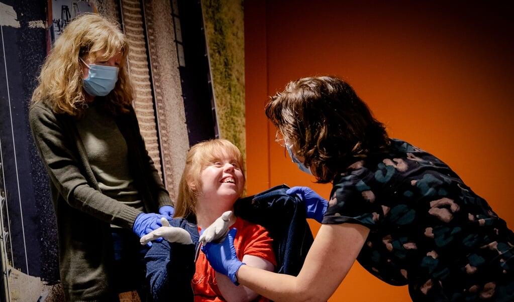 Sanne krijgt het vaccin toegediend. In haar woonzorgcentrum, voor mensen met een verstandelijke beperking, is een begin gemaakt met vaccineren.  (beeld anp / Robin van Lonkhuijsen)