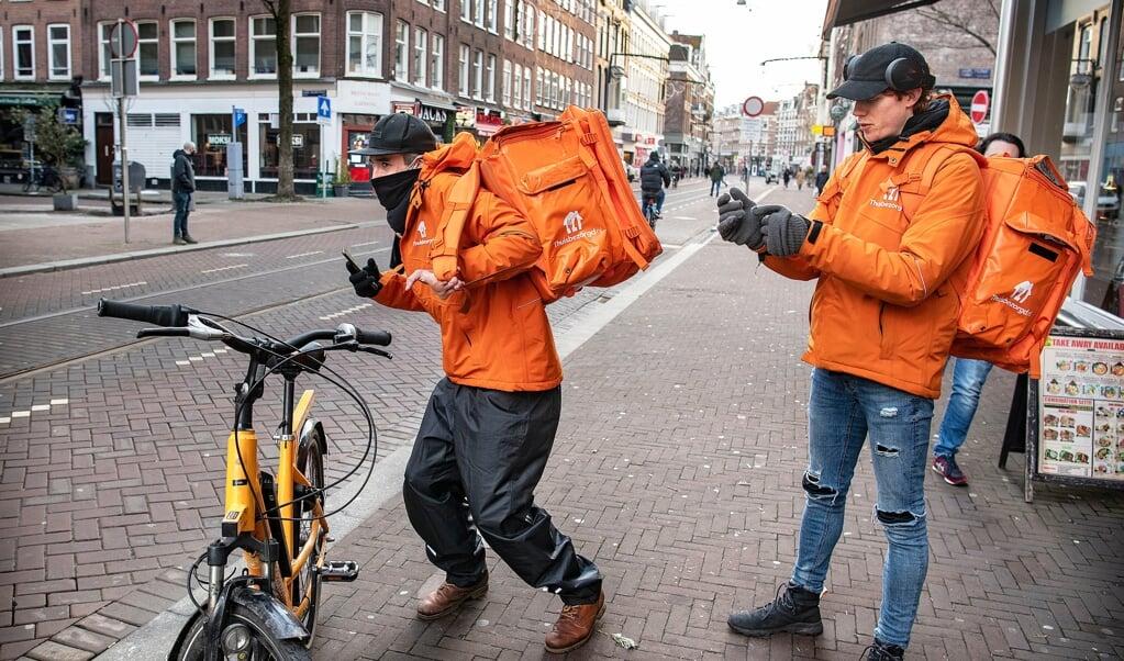 Twee bezorgers van Thuisbezorgd.nl gaan op pad met hun bestelling.  (beeld Guus Dubbelman)