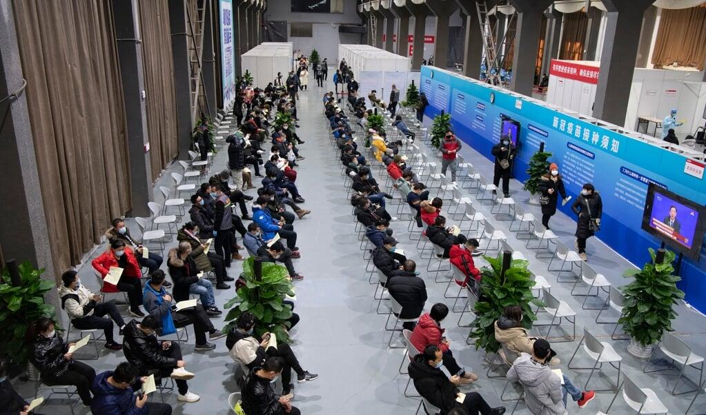 In Peking wachten inwoners geduldig op de inenting tegen het corona-virus. Binnen nu en drie weken moeten 50 miljoen Chinezen zijn gevaccineerd.  (beeld afp)