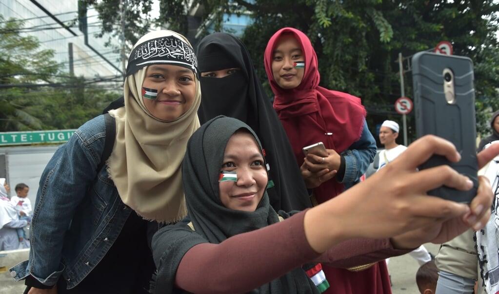 De MUI, de belangrijkste raad van geestelijken in Indonesië, organiseerde in 2017 een demonstratie tegen Donald Trump. Vier deelnemende vrouwen maken een selfie.  (beeld / afp Photo / Adek Berry)