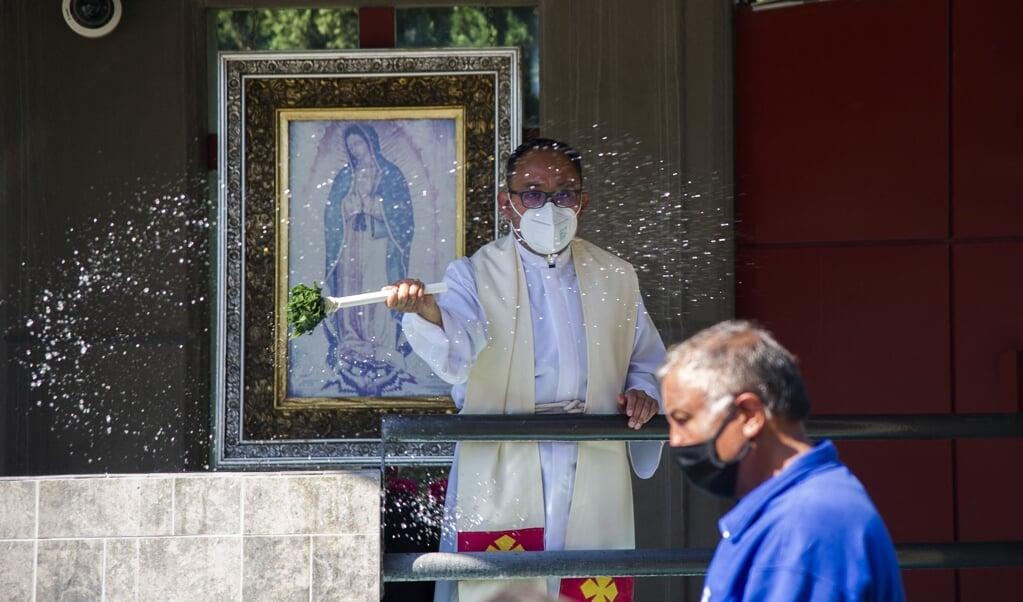 Een priester met mondkapje zegent de gelovigen in Mexico-Stad. Steeds minder Mexicanen noemen zich rooms-katholiek.  (beeld afp / Claudio Cruz)