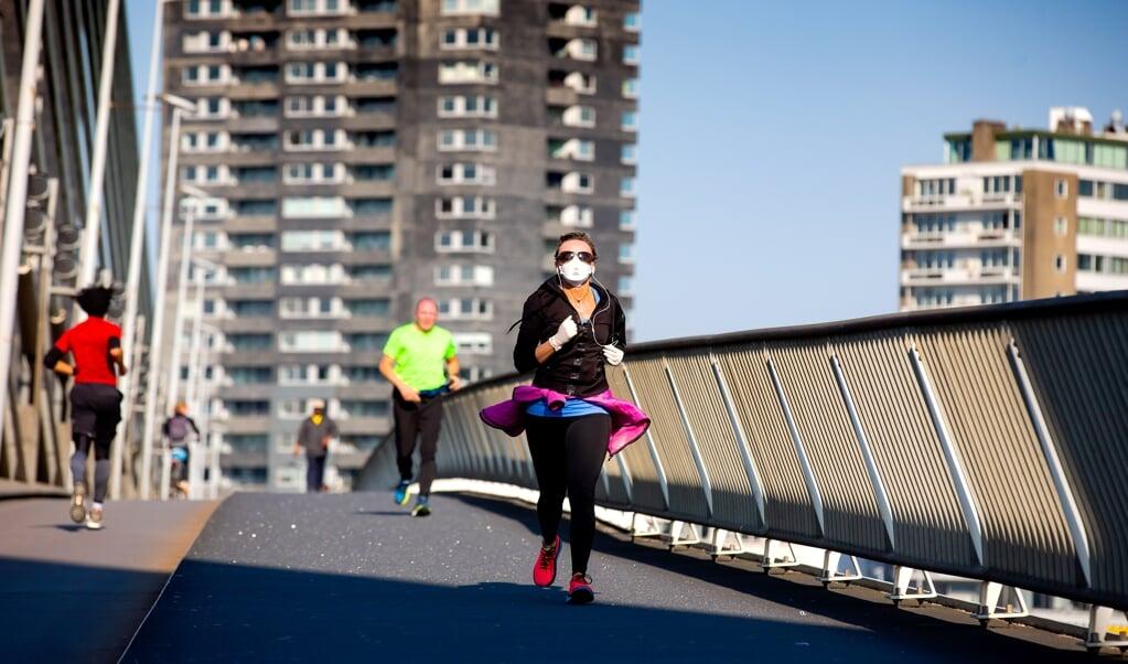 Hardlopers lopen over de Erasmusbrug in Rotterdam. Inmiddels telt Nederland meer dan een miljoen recreatieve hardlopers, aldus Olivier Heimel.  (beeld anp / Bart Hoogveld)