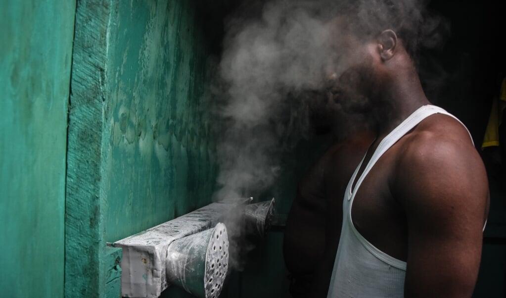Kruidendokter Masafiri Mjema heeft een sauna-achtige ruimte geïnstalleerd waar voorbijgangers voor 35 eurocent tien minuten stoom kunnen inademen.  (beeld afp / Ericky Boniphace)
