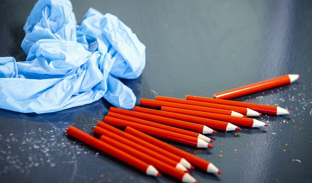 Rode potloden en wegwerphandschoentjes in een model-stembureau in Rotterdam Charlois. Iedereen die een stem uit gaat brengen krijgt een eigen potlood. Voor de Tweede Kamerverkiezingen moeten alle stembureaus coronaproof worden ingericht.  (beeld anp / Sem van der Wal)