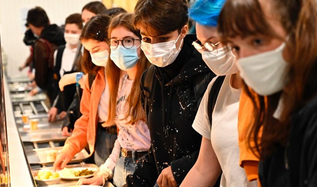Scholieren met mondmaskers op in een Franse schoolkantine.  (beeld afp / Damien Meyer)