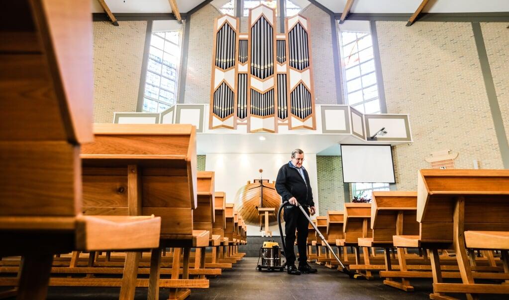 Boudewijn Tims zuigt de kerkvloer van De Ark op Urk.  (beeld Maarten Boersema)