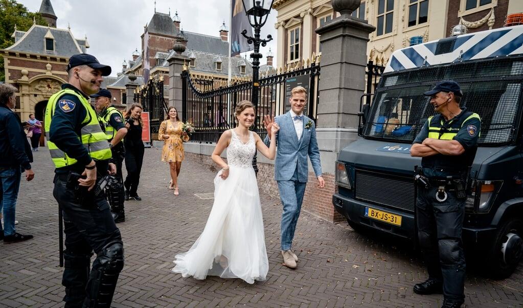 Een bruidspaar loopt langs agenten op het Binnenhof.  (beeld anp / Bart Maat)