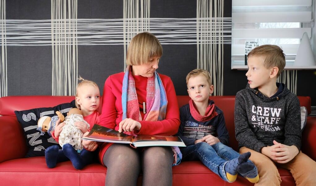 Margreet van den Berg leest voor uit een kinderbijbel, aan Krista (2), Hielke (5) en haar eigen zoon Wout (8).  (beeld Dick Vos)