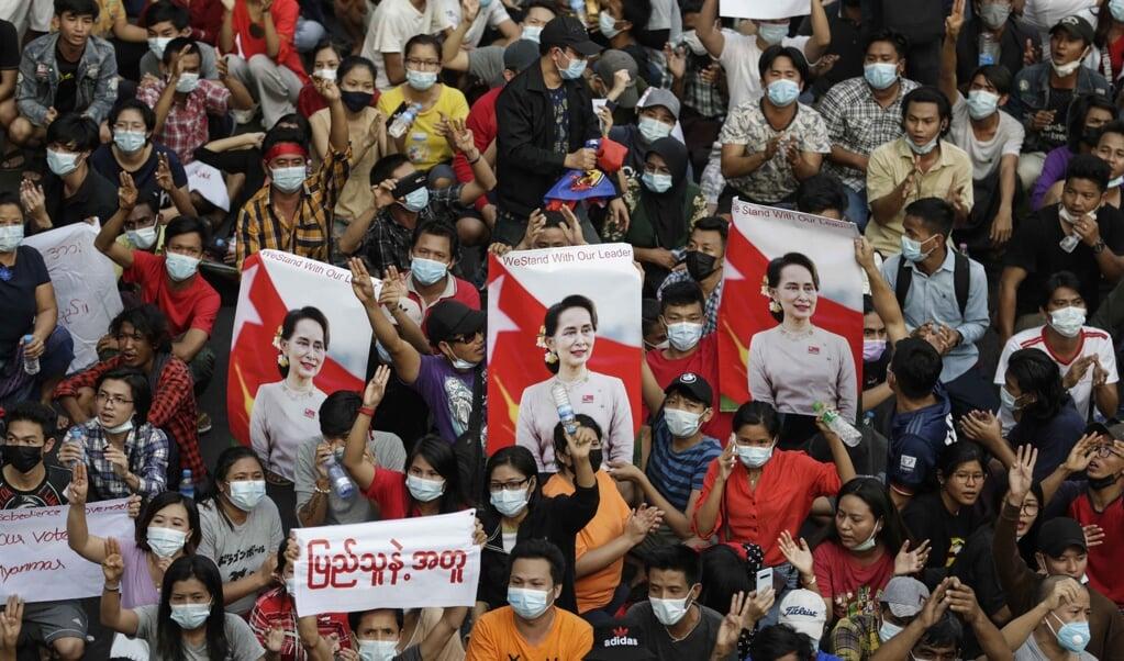 Demonstranten met foto's van Aung San Suu Kyi keren zich tegen de junta in de straten van Yangon.  (beeld epa / Lynn Bo Bo)