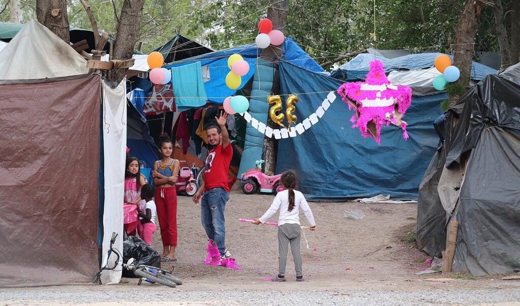 Migranten vieren een verjaardag in Kamp Matamoros in het noordoosten van Mexico. Op een halve vierkante kilometer wonen naar schatting zevenhonderd mensen in bouwsels van zeil en houten palen.   (beeld epa / Abraham Pineda-Jacome)