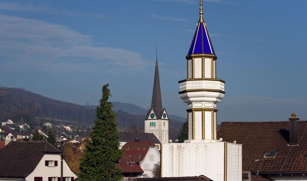 Minaret en kerktoren in een Zwitsers dorp. Volgens Olivier Roy groeit in Europa een praktijk om alles wat religieus lijkt in het publiek domein te verbieden,  (beeld afp / Fabrice Coffrini)