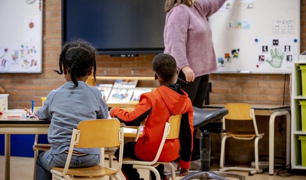 Leerlingen van de Van Houteschool voor speciaal basisonderwijs aan het werk. Een aantal kinderen gaat ondanks de lockdown toch naar school.  (beeld anp / Robin van Lonkhuijsen)
