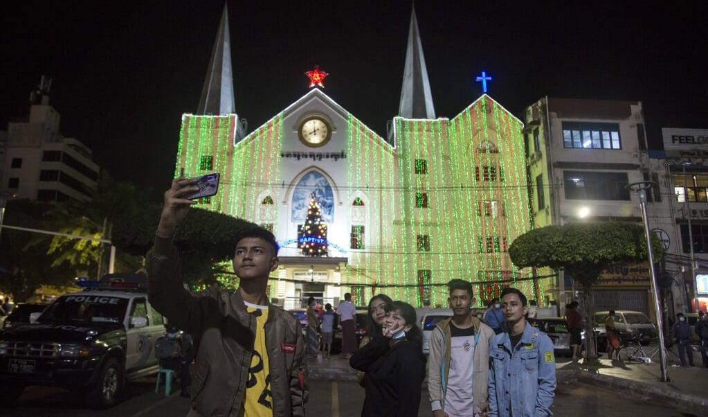 Jongeren nemen een selfie bij de Immanuel Baptist kerk in Yangon (Rangoon), de voormalige hoofdstad van Myanmar (Birma).  (beeld afp / Sai Aung Main)
