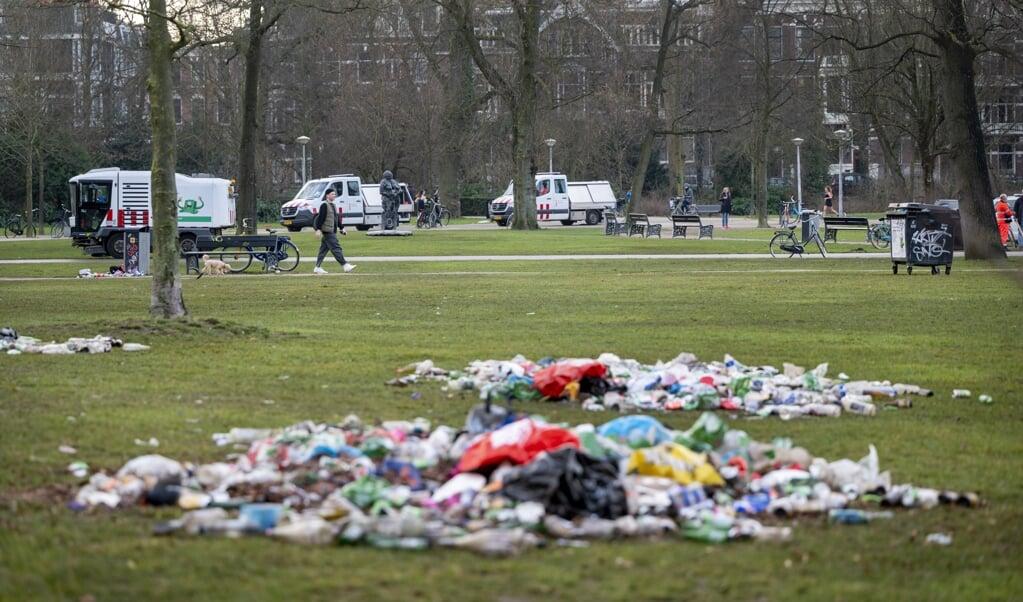 Gemeentemedewerkers hebben het afval bij elkaar geruimd dat werd achtergelaten door bezoekers van het Vondelpark. De politie greep er eerder in omdat het in het park te druk was en de coronamaatregelen niet werden nageleefd.  (beeld anp / Evert Elzinga)