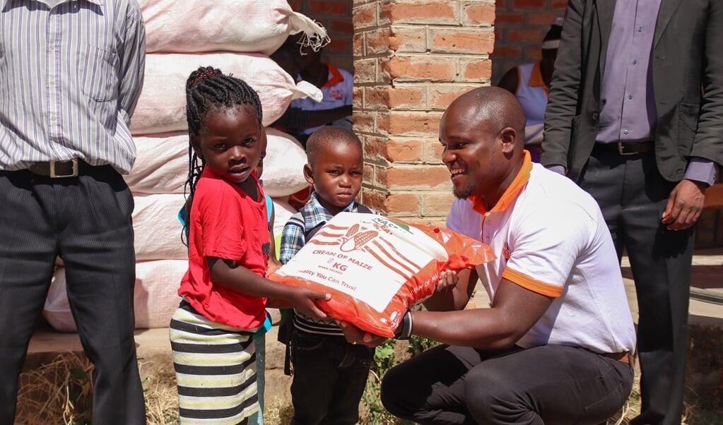 Hulpverlener Sungeni Ngonamo van Red een Kind geeft extra voedselhulp aan jonge gezinnen in Malawi tijdens de coronapandemie.  (beeld Anneke Jagau)