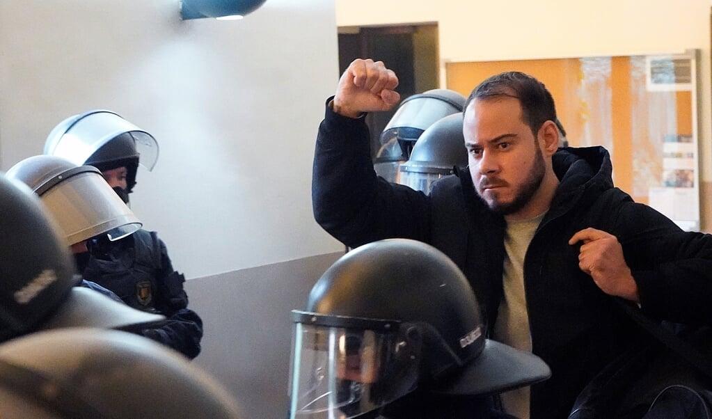 Met opgeheven vuist richt Pablo Hasél zich tot een groepje journalisten, terwijl hij uit het gebouw van de universiteit van Lleida afgevoerd wordt door een dozijn agenten van de oproerpolitie.  (beeld epa / Paul de la Calle)