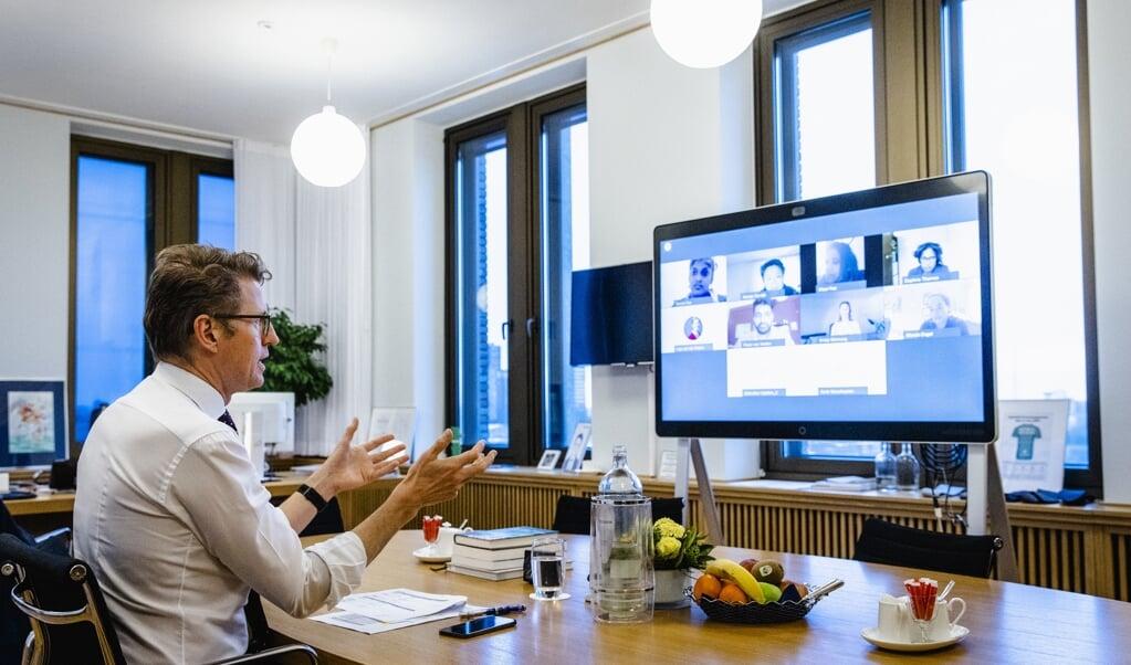 Sander Dekker, demissionair minister voor Rechtsbescherming, praat online met belangengroepen over het opschorten van interlandelijke adoptie.  (beeld anp / Sem van der Wal)