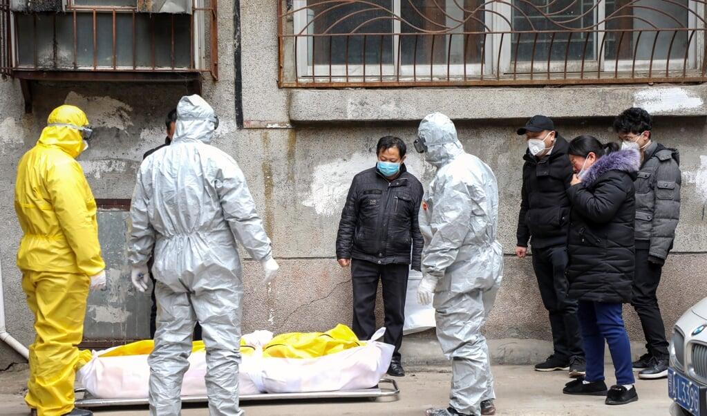 Begin februari 2020 halen uitvaartverzorgers in Wuhan het lichaam op van een man die vermoedelijk aan corona is overleden.  (beeld epa / Yuan Zheng)