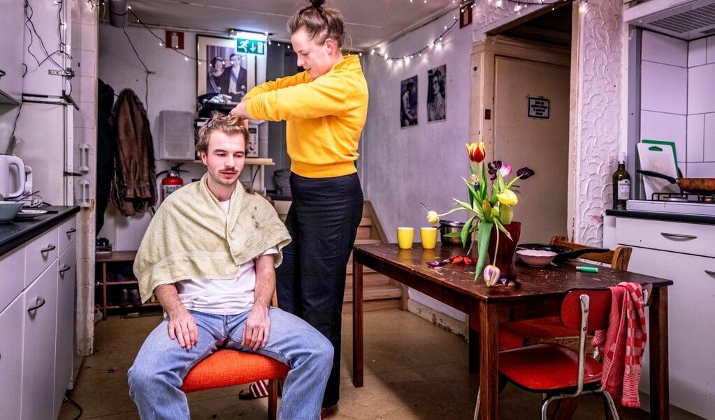 Gelegenheidskapper Yara Piekema voorziet Adriaan Walpot, een van haar dertien huisgenoten, van een nieuw kapsel.   (beeld Raymond Rutting )